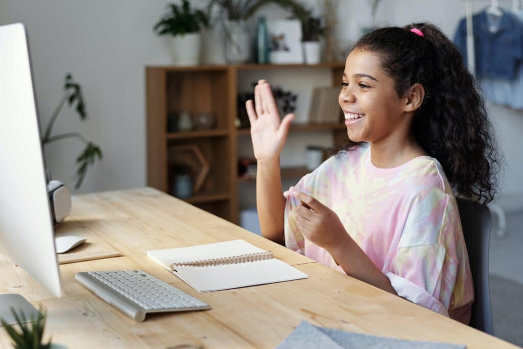 Young girl attending virtual school on laptop