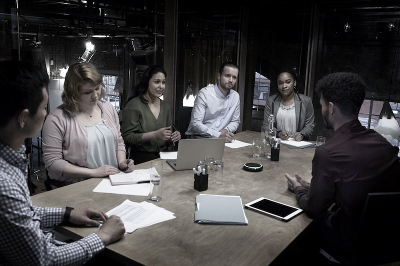employees having a meeting using the shure MXA 310 table array microphone