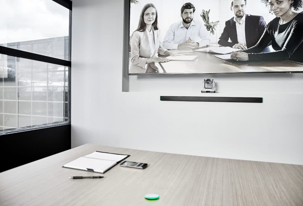 meeting space with MXA710 linear array microphone mounted on wall beneath display and MXA-NMB on the work table